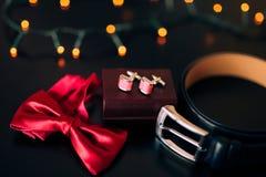 Zapatos negros del novio, corbata de lazo roja, mancuernas, correa, en un bla Imagenes de archivo