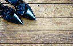 Zapatos negros del tacón alto en la madera Fotos de archivo libres de regalías