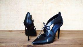 Zapatos negros del tacón alto en la madera Fotos de archivo