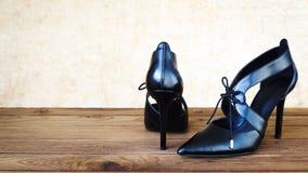 Zapatos negros del tacón alto en la madera Imágenes de archivo libres de regalías