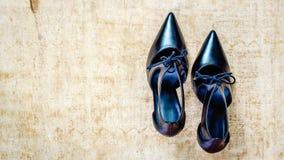 Zapatos negros del tacón alto en la madera sucia Imagen de archivo