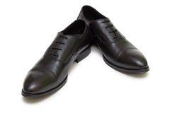 Zapatos negros en el fondo blanco Foto de archivo libre de regalías