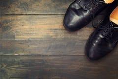 Zapatos negros en el fondo de madera fotografía de archivo