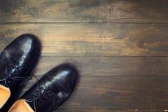 Zapatos negros en el fondo de madera imagen de archivo