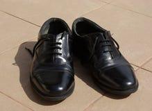 Zapatos negros en el sol imagen de archivo