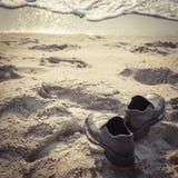 Zapatos negros en la playa fotos de archivo libres de regalías