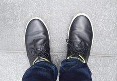 Zapatos negros en la tierra Imagen de archivo libre de regalías