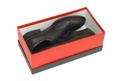 Zapatos negros en rectángulo rojo en el fondo blanco Imagen de archivo