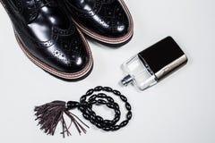 Zapatos negros masculinos con perfume y accesorios Imagen de archivo libre de regalías