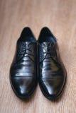 Zapatos negros para hombre de moda en un piso imagenes de archivo