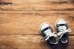 Zapatos negros para los niños en el piso de madera para la forma de vida Imágenes de archivo libres de regalías