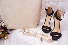 Zapatos negros, parte de un bolso beige del ` s de las mujeres, en la piel blanca concepto de moda Fotos de archivo