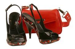 Zapatos negros y bolso rojo fotos de archivo