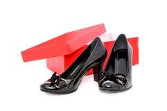 Zapatos negros y caja roja fotos de archivo