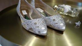 Zapatos nupciales de la boda con gomas y pendientes de la joyería en fondo de oro almacen de metraje de vídeo