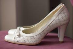 Zapatos nupciales de la bomba blanca colocados en una tabla rosada oscura Imagenes de archivo