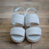 Zapatos nupciales en piso de madera Foto de archivo
