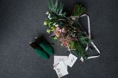 Zapatos nupciales verdes, ramo verde rico de la boda con las cintas rosadas y una mentira elogiosa de la boda en un piso gris Fotografía de archivo