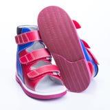 Zapatos ortopédicos del ` s de los niños en un fondo blanco Foto de archivo