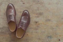 Zapatos para hombre de cuero marrones clásicos en fondo de madera Imagen de archivo libre de regalías