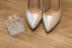 Zapatos para la novia en plata y una botella de perfume, de zapatos formales del tacón alto, de accesorios en un fondo de madera, Foto de archivo libre de regalías
