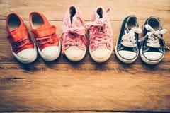 Zapatos para los niños en el piso de madera - forma de vida Imágenes de archivo libres de regalías