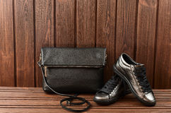 Zapatos para mujer metálicos del cuero superior y bolso de cuero negro en bro Fotografía de archivo libre de regalías