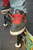 Zapatos, pies y tarjeta del patinador Imagen de archivo
