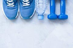 Zapatos planos del deporte de la endecha, botella de agua y pesas de gimnasia fotos de archivo libres de regalías