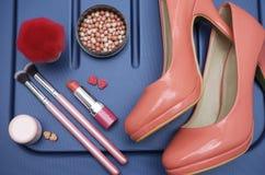 Zapatos, producto cosmético y accesorios de la belleza para la mujer, en un fondo del color del azul real Fotografía de archivo libre de regalías