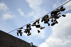 Zapatos que cuelgan por un hilo en una calle fotografía de archivo