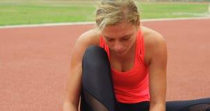 Zapatos que llevan del atleta de sexo femenino en la pista de funcionamiento 4k almacen de video
