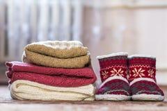 Zapatos rojos con el modelo del Año Nuevo y una pila de suéteres hechos punto Foto de archivo libre de regalías