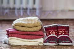 Zapatos rojos con el modelo del Año Nuevo y una pila de suéteres hechos punto Fotos de archivo
