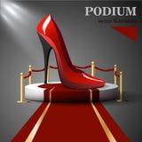 Zapatos rojos con los talones que se colocan en el podio Imagen de archivo