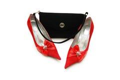 Zapatos rojos de la mujer y bolso negro aislados Foto de archivo libre de regalías