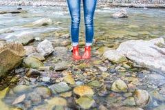 Zapatos rojos de las mujeres en el agua en las montañas cárpatas imagen de archivo libre de regalías