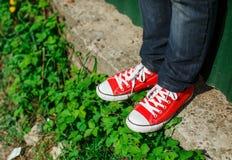 Zapatos rojos de las zapatillas de deporte en el hormigón Fotos de archivo