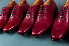 Zapatos rojos de Oxford en fondo azul Tres abarcas de los pares Imagen de archivo libre de regalías