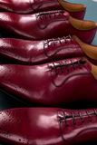Zapatos rojos de Oxford en fondo azul Tres abarcas de los pares Cierre para arriba Imágenes de archivo libres de regalías