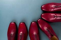 Zapatos rojos de Oxford en fondo azul Tres abarcas de los pares Visión superior Imagen de archivo libre de regalías