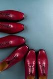 Zapatos rojos de Oxford en fondo azul Tres abarcas de los pares Visión superior Fotos de archivo