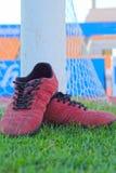 Zapatos rojos en hierba verde con fútbol de la meta Foto de archivo