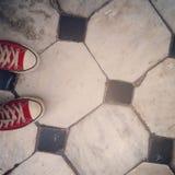 Zapatos rojos en suelo de baldosas blanco y negro Imagen de archivo