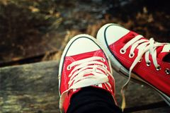 Zapatos rojos en un piso de madera - zapatillas de deporte Imagenes de archivo