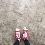 Zapatos rojos que caminan en la visión superior concreta sucia, zapatos de las zapatillas de deporte de lona que caminan en el ho Fotos de archivo libres de regalías