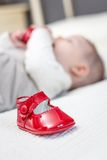 Zapatos rojos y bebé del bebé que juegan en el fondo Imagenes de archivo