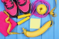Zapatos rosados del deporte, frutas frescas y accesorios para la aptitud en tableros azules, espacio de la copia para el texto en Imagen de archivo libre de regalías