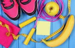 Zapatos rosados del deporte, frutas frescas y accesorios para la aptitud en tableros azules, espacio de la copia para el texto en Imagenes de archivo