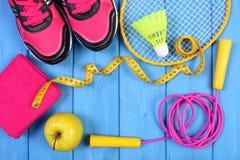 Zapatos rosados del deporte, manzana fresca y accesorios para el deporte en tableros azules, espacio de la copia para el texto Fotos de archivo libres de regalías